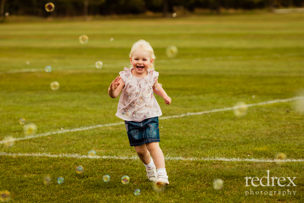 Toddler in park with bubbles