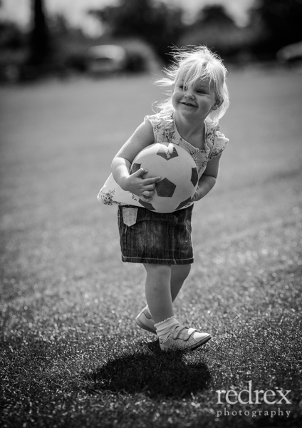 Toddler with football in the park